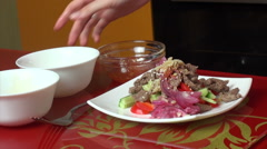 Pour sauce spicy Thai salad with beef and vegetables Stock Footage