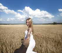 Stock Photo of Follow me, Beautiful sexy young woman holds the hand of a man in a wheat fiel