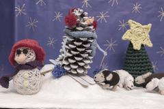 Xmas decorations crafts snow scenary crochet snowman, skier, sheep and tree - stock photo