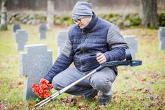 Disabled veteran with crutches near to the tomb monument with flowers - stock photo