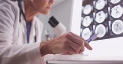 Intelligent female radiologist analyzing with microscope - stock footage