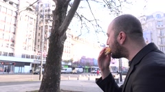 Business man on bench after long day eating hamburger and looking at buildings Stock Footage