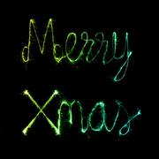 Merry Xmas made of sparkles firework at nigh Kuvituskuvat