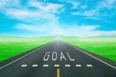 road through the green field with sign goal on asphalt - stock photo