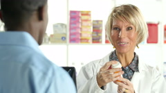 Female pharmacist explaining prescription to male customer, close up Stock Footage