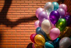 Multi-colored balloons on brick wall background - stock photo