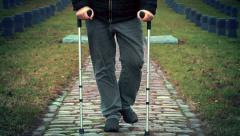 Disabled veteran on crutches walking at cemetery - stock footage
