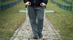 Disabled veteran on crutches walking away at cemetery - stock footage