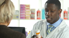 Pharmacist entering customer information into computer, close up - stock footage