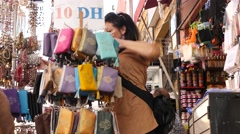 Woman choosing goods for purchase in Marrakesh street Stock Footage