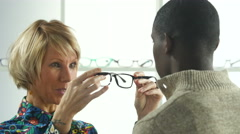Female optician helping male customer select eye glasses - stock footage