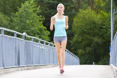 Young running woman trains her stamina outdoor Stock Photos
