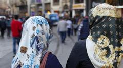 Two women in scarves walk in Istanbul Stock Footage