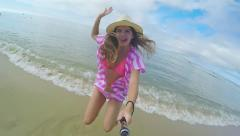Excited Teen Girl Jumps For Joy With Gopro Stick, Waves Crash At Her Feet Stock Footage