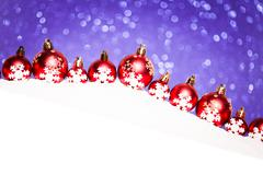 christmas red balls in snow on purple glitter background - stock photo