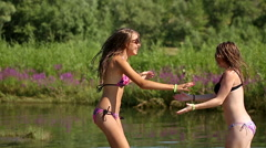 Girlfriends having fun and jumping on the river beach. Best friends. BFF - stock footage