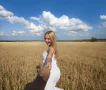 Follow me, Beautiful sexy young woman holds the hand of a man in a wheat fiel - stock photo