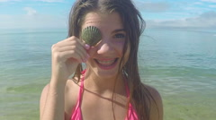 Portrait Of Teen Girl, She Holds Up Seashell Over One Eye, Then She Winks Stock Footage