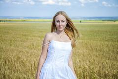 Beautiful young blonde woman against the backdrop of the vast fields of wheat Stock Photos
