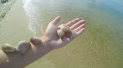 Teenage Girl Holds Out Her Arm And Displays Seashells, Collected From The Beach Stock Footage