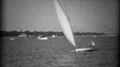 1934: Small sailboat taking 2 passengers across the gentle bay waters. BILOXI, - stock footage