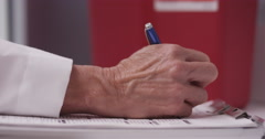 Doctor's hand writing notes - stock footage