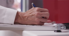 Close-up of doctor's hand writing on a clipboard - stock footage
