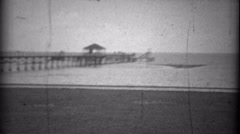 1934: Beach pier sandy view gulf coast sandy bay waters. BILOXI, MISSISSIPPI - stock footage