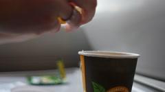 Adding liquid lemon to tea on the train - stock footage