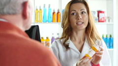 Female pharmacist explaining prescription drug to senior male Stock Footage