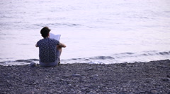 A guy reading a book sitting on beach Stock Footage
