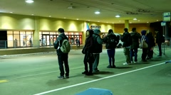 People line up for waiting bus at bus station Stock Footage