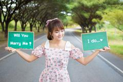 """Cute woman hand holding green board sign with text """" will you marry me"""" Stock Photos"""