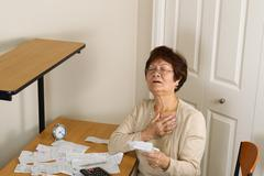 Stock Photo of Older woman feeling illness with her financial bills