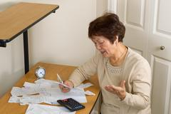 Older woman frustrated by all her financial bills - stock photo