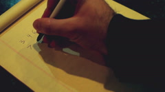 Writing numbers down on paper Stock Footage