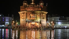 Sikhs and indian people visiting the Golden Temple in Amritsar at night. India - stock footage