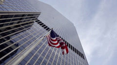American Flag waving underneath skyscraper - panning with upward angle of sky NY Stock Footage