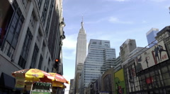 34th street Manhattan hot dog vendor people crossing Empire State Building NYC - stock footage