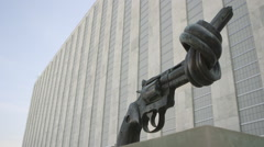 Non-vilolence sculpture of gun with knotter barrel at United Nations in Stock Footage
