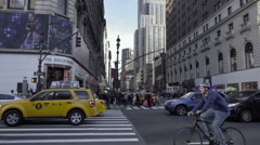 Man on bicycle riding in heavy Midtown Manhattan traffic among cars in NYC Stock Footage