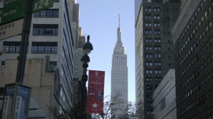 Empire State Building panning down to NYPD police car on 34th Street Manhattan Stock Footage
