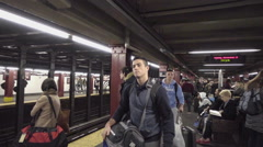 Crowded subway platform passengers waiting for train carrying bags luggage NYC Stock Footage