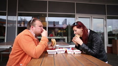 Woman and man eating burger in a fast food Stock Footage