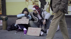 Homeless couple struggling with help signs, poverty sucks, people in street Stock Footage