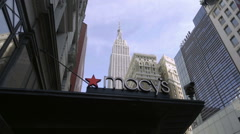 Tilting down from Empire State Building and Macy's sign to people, shoppers NYC Stock Footage