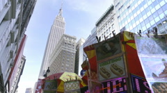 Food truck in the shadow of Empire State Building in Manhattan tilting down NYC Stock Footage