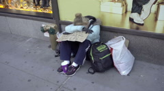Homeless woman with help sign and backpack sitting on sidewalk on NYC street Stock Footage