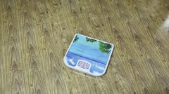 Girl measures weight on floor scales. Close-up socks Stock Footage