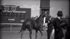 1935: Black man handling horse at race gets glare from white owner. HIALEAH, Stock Footage